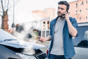 man-holding-phone-car-accident