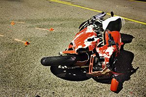 crashed red motorcycle with damaged fairing