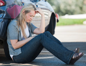 woman leaning on a car after an accident